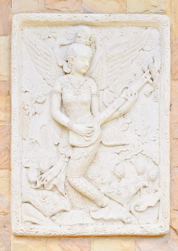 Statue of a woman playing fiddle . Thai ancient stone carving