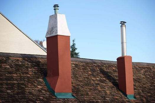 A shingle roof with two new chimneys and protruding stainless steel tubes.