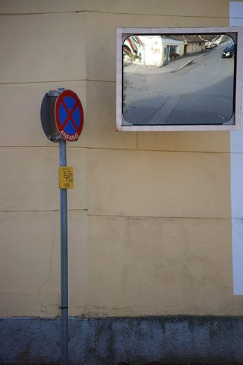 On the buildings of a blind crossing hangs a traffic mirror and stands a no entry sign.