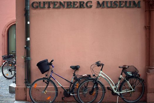 Mainz, Germany - September 04, 2015: Bicycles standing under the entrance sign of the Gutenberg Museum on September 04, 2015 in Mainz.