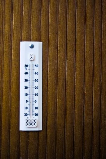 room thermometer on a wooden wall close up