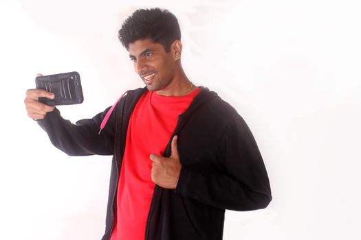 indian teenager taking selfies with his mobile phone