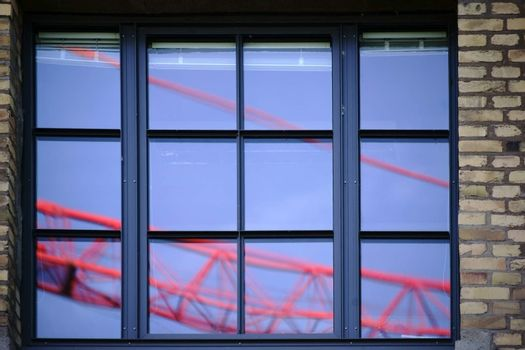 The boom of a construction crane reflected in the glass of windows.