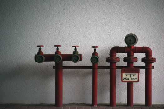 Fire water connections and pipes in red signal color on the wall of an industrial building.