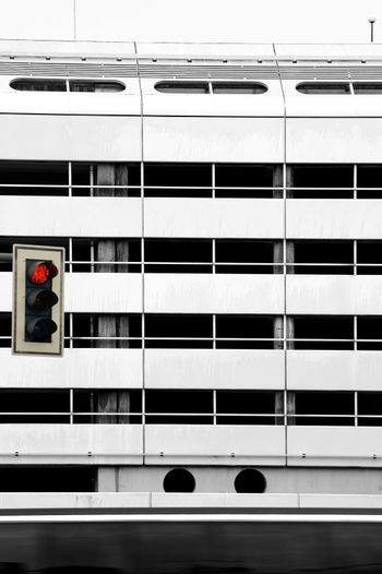 A bus is passing a striking facade made of metal, in front of a red light.