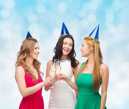 drinks, holidays, people and celebration concept - smiling women in party hats with glasses of sparkling wine over blue lights background