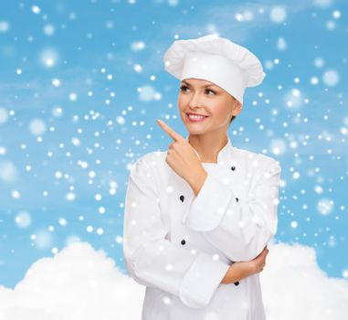 smiling female chef dreaming pointing finger up
