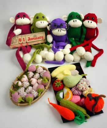 Family of stuffed animal sit at new year party, group of knitted monkey in colorful yarn, symbol of 2016, funny homemade toy on white background, handmade food and calendar to happy new year