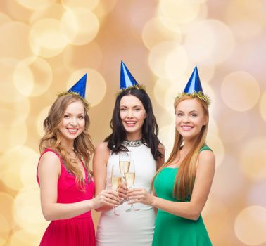 drinks, holidays, people and celebration concept - smiling women in party hats with glasses of sparkling wine over beige lights background