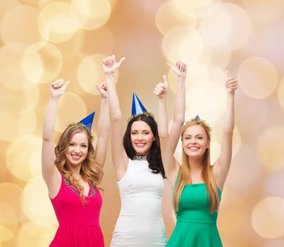 holidays, people, gesture and celebration concept - smiling women in party caps showing thumbs up over beige lights background