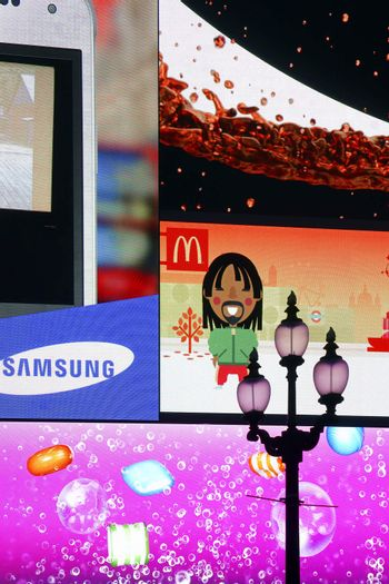 London, UK - November 28, 2014: A nostalgic lantern faces the large advertising space of Piccadilly Circus with pixel-like colorful advertising of different brands on November 28, 2014 in London.