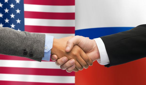 handshake over american and russian flags