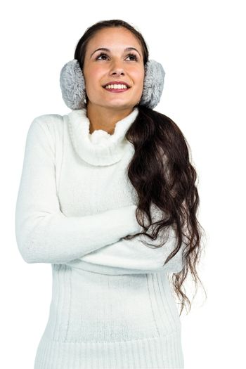 Smiling woman with earmuffs crossing arms and looking up