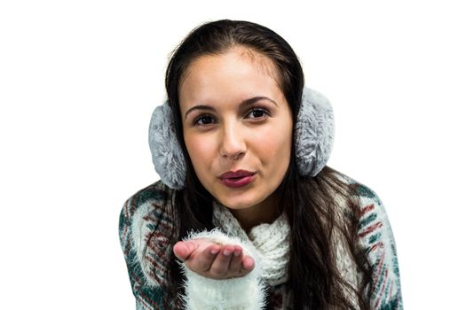 Smiling woman with earmuffs blowing kiss