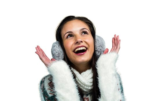 Smiling woman with earmuffs looking up