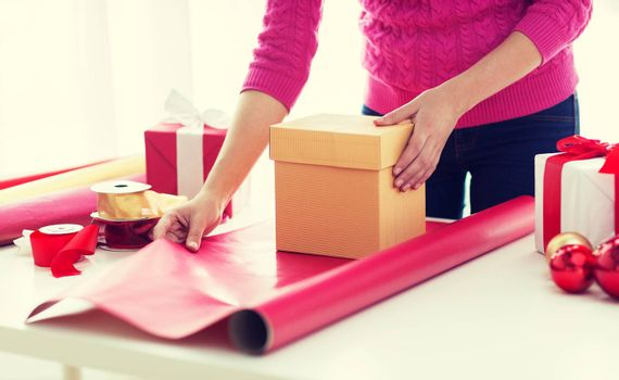 holidays, people and celebration concept - close up of woman decorating christmas presents