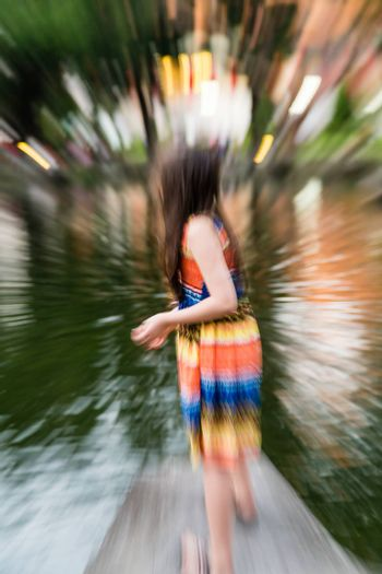 Young girl in colorful dress by lake, defocused