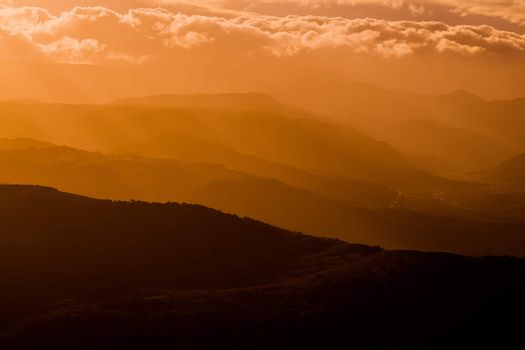 mountains silhouette at sunset with fog