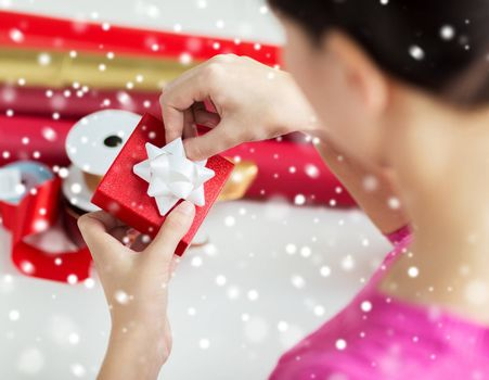 holidays, people and celebration concept - close up of woman decorating christmas present at home