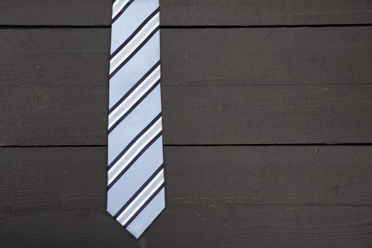 Striped business tie on dark wooden background