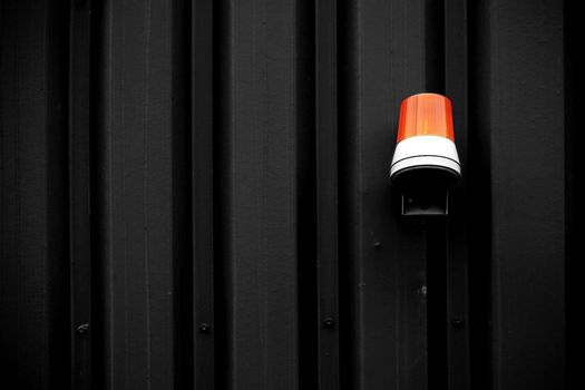 The photograph of a yellow warning light on an intensely colored corrugated iron wall.