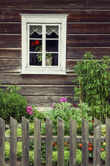Window picture of an old traditional wooden log house. Wooden fence and garden with flowers is also seen