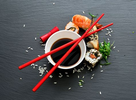Sushi with soy in saucers on a slate table