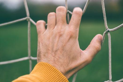 Male hand holding soccer net
