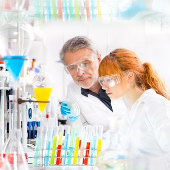 Attractive young female scientist and her senior male supervisor looking at the cell colony grown in the petri dish in the life science research laboratory