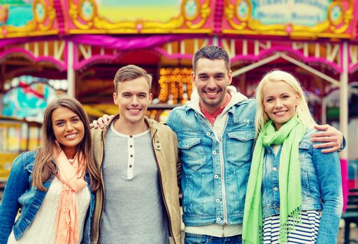 group of smiling friends in amusement park