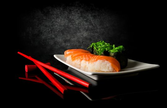 Sushi and chopsticks on a black background