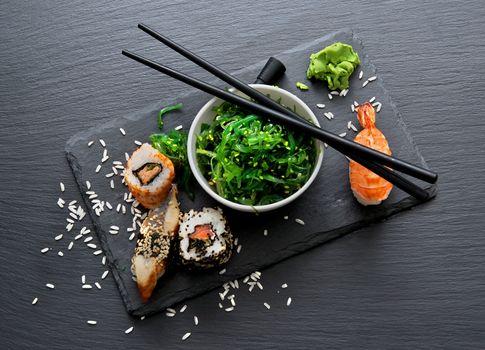 Sushi and seaweed salad on slate table