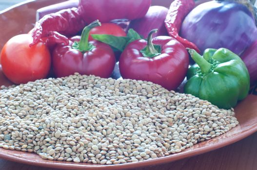 Lentils ready to be cooked with tomatoes , peppers , eggplant