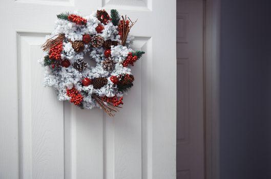 White door with Christmas wreath. Horizontal photo