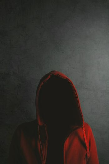 Unrecognizable person wearing red hooded shirt