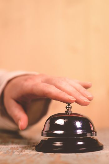 Woman ringing hotel service bell on reception desk