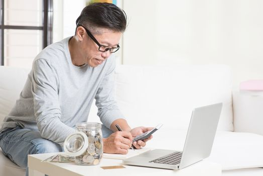 Asian mature man counting on money using calculator and laptop computer. Saving, retirement, retirees financial planning concept.