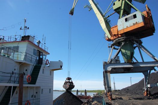 Dockside cargo crane loads coal at river port Kolyma