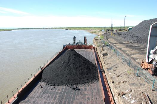 Barge with coal at river port Kolyma