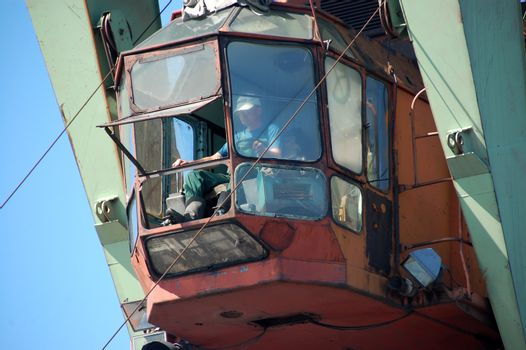 Dockside cargo crane operator at river port Kolyma