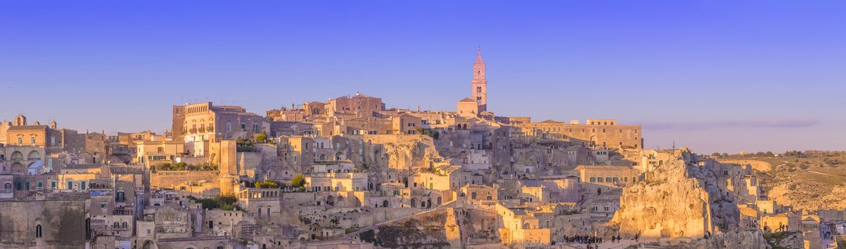 panoramic view of typical stones and church of Matera and the Madonna de Idris under begin sunset sky