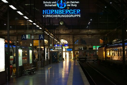 Frankfurt, Germany - November 14, 2015: The main railway station of Frankfurt indoors at night with a large neon sign of the N�rnberger Insurance Company above the entrance on November 14, 2015 in Frankfurt.
