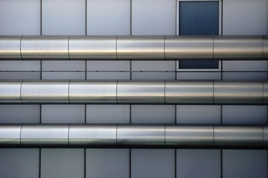 Three parallel-mounted stainless steel pipes at a symmetrically arranged metal facade.