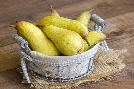 Juicy fresh pears in a basket on dark wooden background