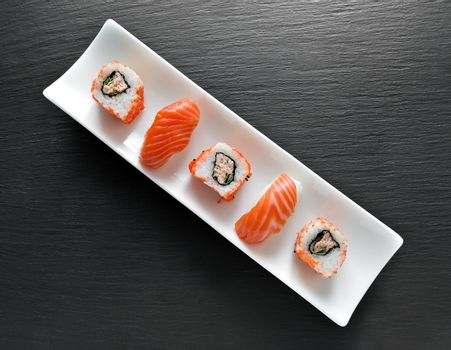 Sushi and rolls on a rectangular white plate and slate table