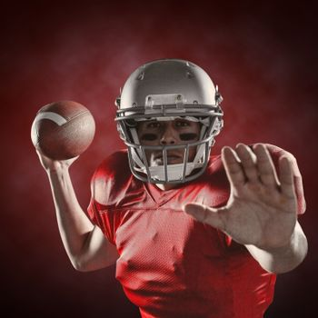 Composite image of portrait of sportsman defending while holding american football