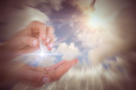 Composite image of woman holding precious gem