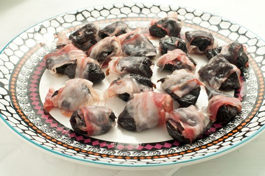 Prunes wrapped in bacon and baked