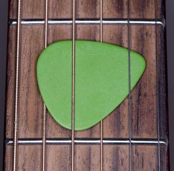 Green Plectrum Stuck in Steel Strings close up macro image.