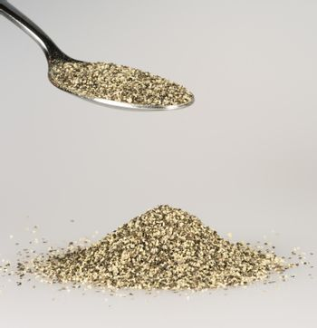 Ground Pepper on Tablespoon with a pile of black pepper beneath.